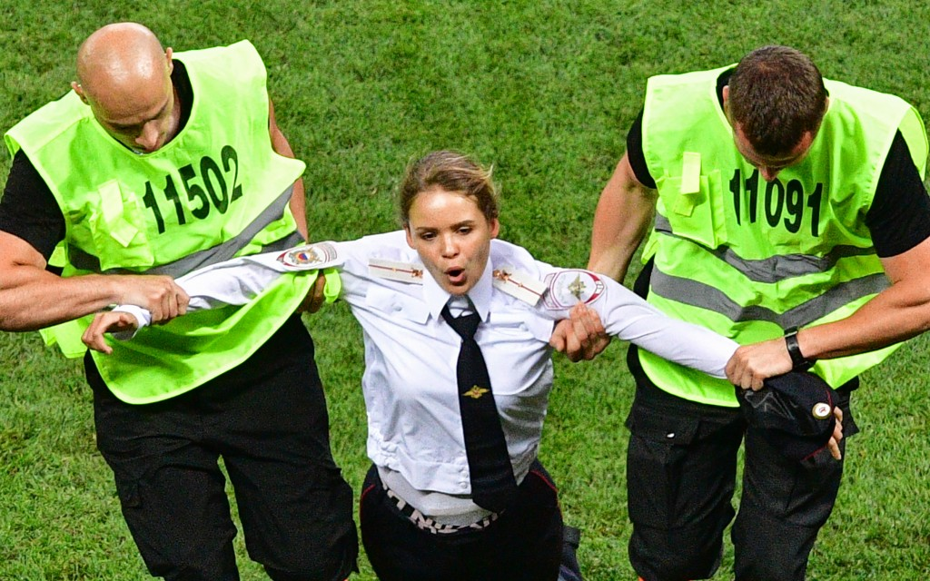 A pitch invader, a member of the Russian protest-art group Pussy Riot, is escorted by stewards during the Russia 2018 World Cup final football match between France and Croatia at the Luzhniki Stadium in Moscow on July 15, 2018. / AFP PHOTO / Mladen ANTONOV / RESTRICTED TO EDITORIAL USE - NO MOBILE PUSH ALERTS/DOWNLOADS